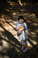 High angle view of girl holding bag with chestnuts in forest