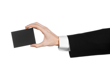 Man in black suit holding a black blank card in hand isolated