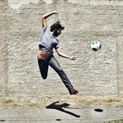 Man playing soccer on street