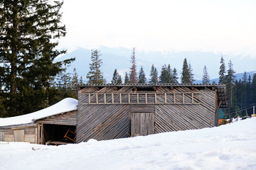 Wooden building in snow, blue sky and mountains on background