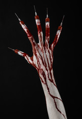 Bloody hand with syringe on the fingers, toes syringes in studio