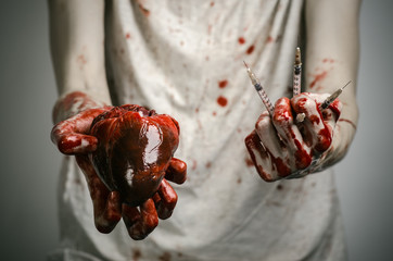 bloody hands addict holding syringe and bloody human heart