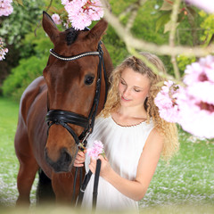Young woman with horse in cherry blossoms