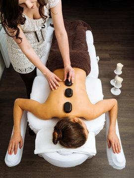 Massage therapist applying a hot stone massage