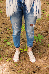 Bohemian fashion woman in ripped denim jeans and canvas shoes