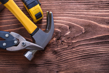 Claw hammer nippers and tape-measure on wood board construction
