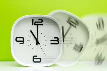 Time is passing by. White clock on green background in motion