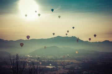 Gruppo di mongolfiere in volo nel cielo al tramonto
