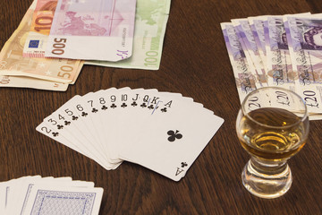Vintage still life of playing cards, cash money and  shot of alc
