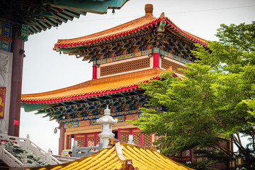 Colorful Buddhist Chinese temple in Thailand with blue sky .