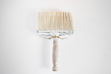 Dirty wall brush on white wall