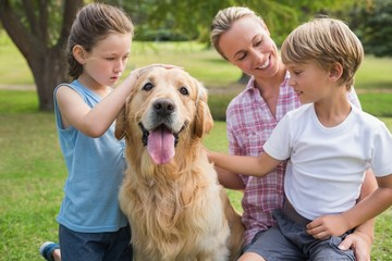 Happy family playing with their dog