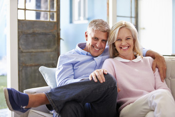 Portrait Of Smiling Mature Couple Sitting On Sofa At Home