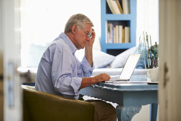 Senior Man At Desk Working In Home Office With Laptop