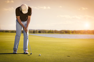 Senior golf player on green with copyspace.