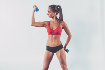 Wall Mural - athletic woman pumping biceps doing workout lifting up dumbbell