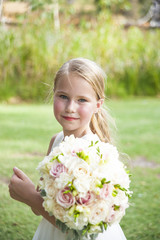 Portrait of Caucasian flower girl with bouquet smiling