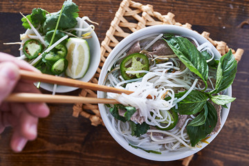 eating a bowl of pho with chopsticks