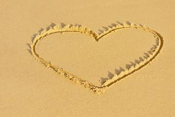 Heart drawn on a sandy beach. Horizontal composition