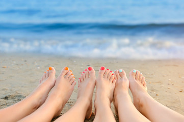 Wall Murals Pedicure Female legs with color pedicure on the background of the sea