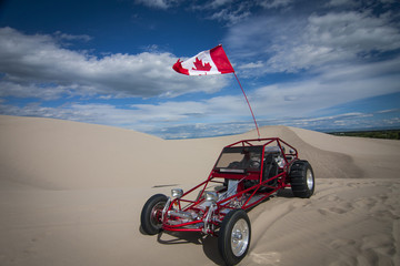 Shiny red sand dune buggy parked in the sand