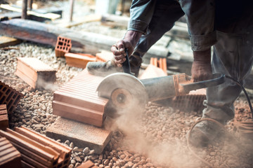 worker using an grinder for cutting construction bricks