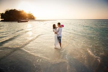 bride and groom hug at spit at sunrise