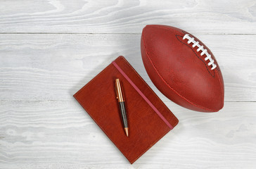 Playbook with Football on rustic white wood