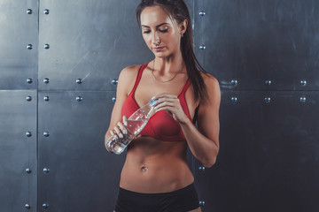 Muscular sporty athlete woman drinking water at the gym after