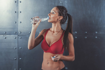 Wall Mural - Muscular sporty athlete woman drinking water at the gym after