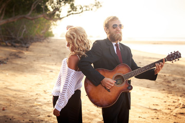 guitarist and blonde girl standing on sandy beach