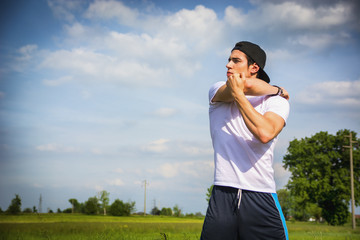 Athletic, fit young man outdoor in country doing stretching