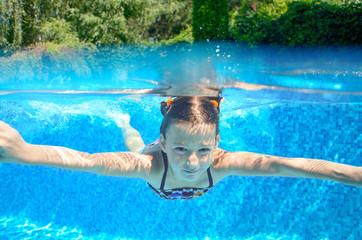 Happy child swims in pool underwater, active kid swimming