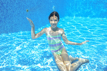 Happy child swims in pool underwater, active kid swimming