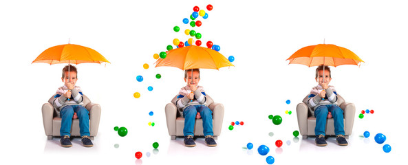 Kid holding an umbrella around colorful balls