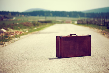Vintage suitcase on the road.