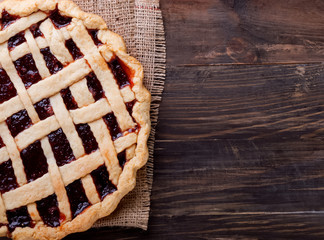 Homemade pie with jam on the wooden table.