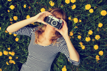 Girl lying in grass, taking a photo.
