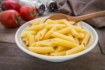 Raw penne pasta in bowl