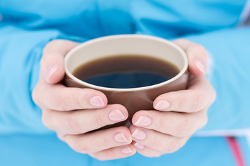 Caucasian woman holding cup of hot tea at winter outdoor.