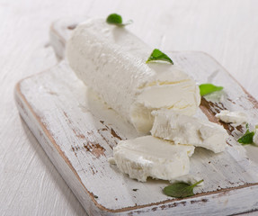 Goat cheese with herbs on  white wooden table
