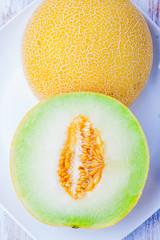 Ripe Galia melon and its slice on plate