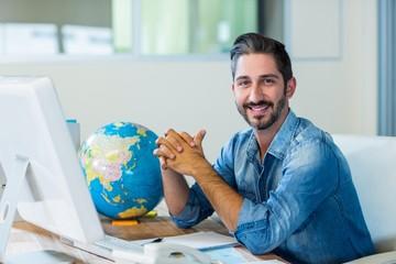 Smiling businessman sitting at his desk