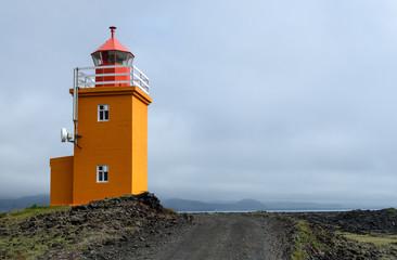 Oranger Leuchtturm an der Küste von Island