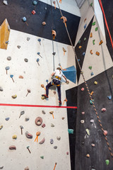 Small girl climbing wall with holding safety rope, indoors