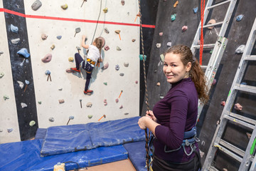 Mother helping her daughter while kid climbing wall in gym