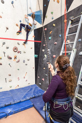 Mother looks her daughter while kid climbing wall with equipment