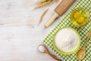 Baking ingredients, rolling pin and wheat ears on wooden table