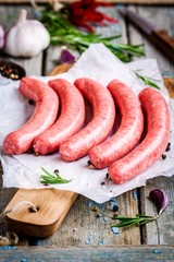 raw homemade sausages on cutting board