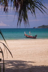 Longboats moored along the tree lined beach of Patong